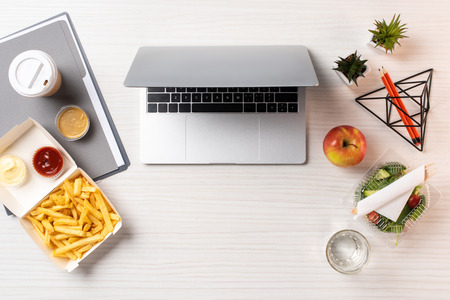 top view of laptop, healthy food and junk food at workplace