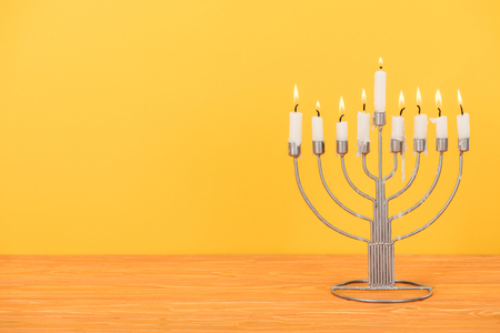 Close up view of menorah with candles for hannukah holiday celebration on wooden tabletop isolated on yellow background, hannukah concept