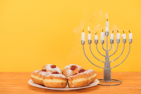 Close up view of sweet doughnuts and menorah with candles on wooden surface isolated on yellow background, hannukah concept