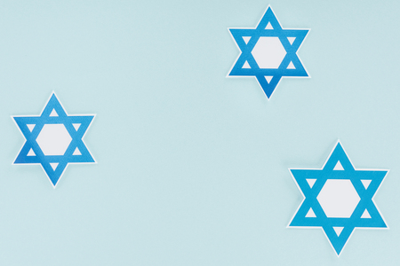 Flat lay with traditional Jewish stars isolated on blue background, hannukah holiday concept Stock Photo
