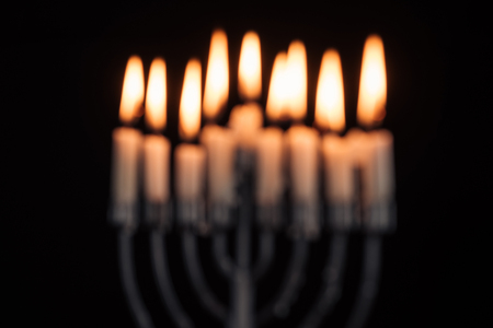 Defocused picture of Jewish menorah with candles for hannukah holiday celebration isolated on black background, hannukah concept Stock Photo