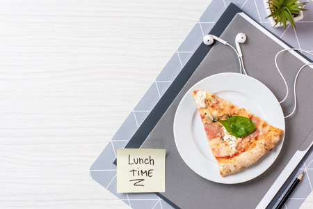 Top view of pizza, earphones and sticky note with inscription lunch time on white wooden table