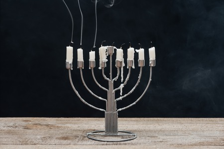 close up view of menorah with candles for hannukah holiday celebration on wooden surface isolated on black, hannukah concept