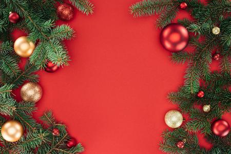 mise à plat avec des branches de pin avec des boules de noël rouges et dorées isolées sur rouge