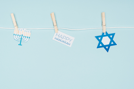top view of hannukah holiday paper signs pegged on rope isolated on blue, hannukah concept