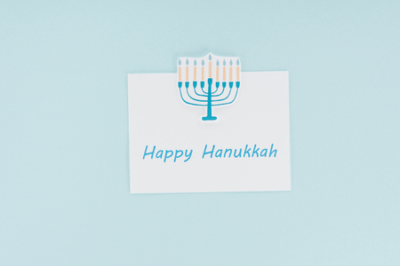 top view of happy hannukah card and paper menorah sign isolated on blue, hannukah concept