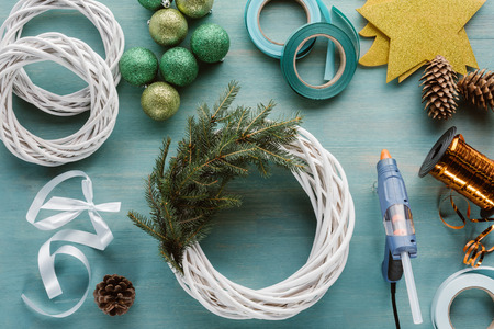 Flat lay with arranged glue gun, Christmas toys and decorations for handmade Christmas wreath on blue wooden tabletop