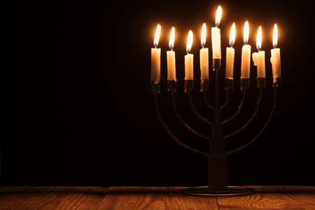 close up view of jewish menorah with candles for hannukah holiday celebration on wooden surface on black backdrop, hannukah concept