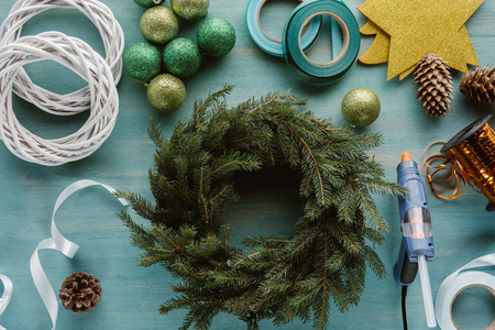 top view of arranged chrismtas toys and decorations for handmade christmas wreath on blue wooden tabletop