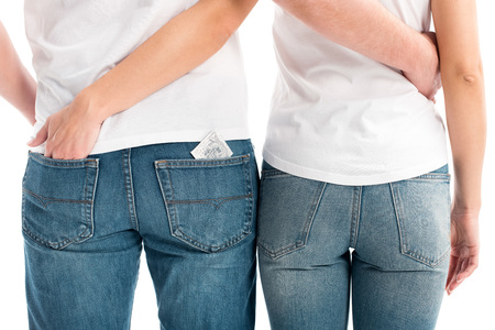 cropped image of heterosexual couple hugging isolated on white, condom in pocket, world aids day concept