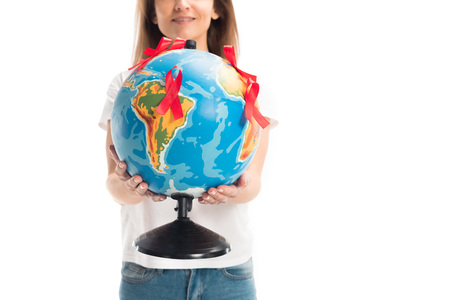 Cropped image of woman holding globe with red ribbons isolated on white background, world aids day concept Stock Photo