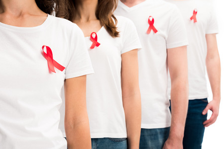 Cropped image of people standing with red ribbons on shirts isolated on white background, world aids day concept