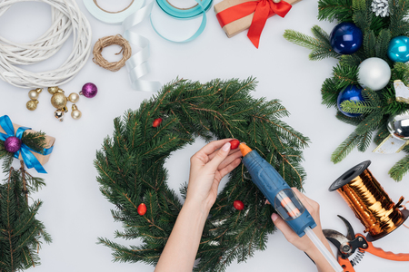 Cropped shot of woman decorating handmade Christmas wreath with briar berries isolated on white background Imagens