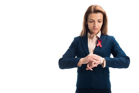 Attractive businesswoman with red ribbon on suit checking time isolated on white background, world aids day concept Stock Photo