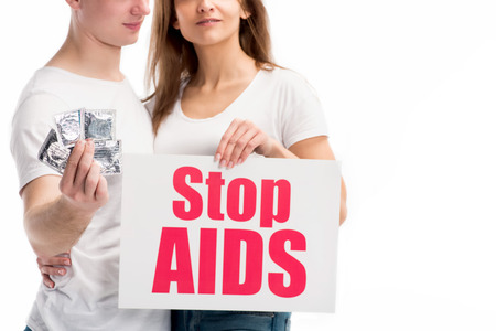 cropped image of boyfriend holding condoms and girlfriend showing card with stop aids text isolated on white Stock Photo