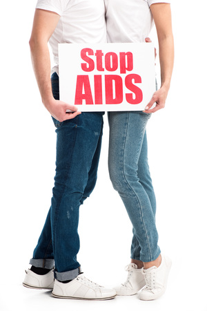 Cropped image of heterosexual couple hugging and holding card with stop aids text isolated on white background