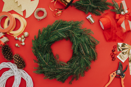 flat lay with pine tree branches arranged in circle and decorations for christmas wreath isolated on red