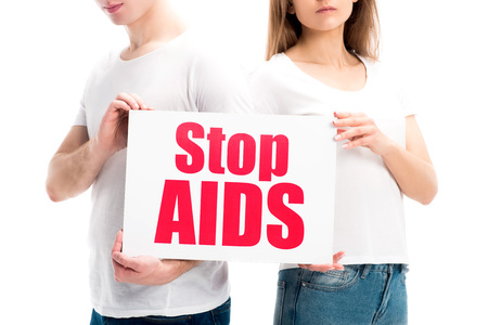 cropped image of heterosexual couple holding card with stop aids text isolated on white, world aids day concept Stock Photo