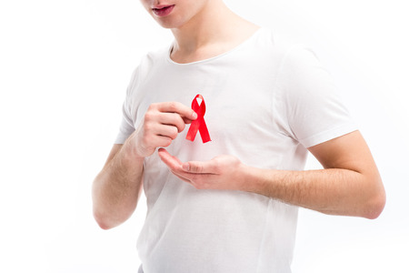 cropped image of young man putting red ribbon on shirt isolated on white, world aids day concept