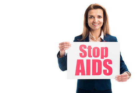 smiling attractive businesswoman showing card with stop aids text isolated on white