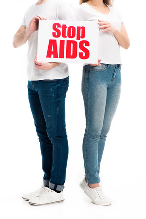 cropped image of heterosexual couple in casual clothes holding card with stop aids text isolated on white