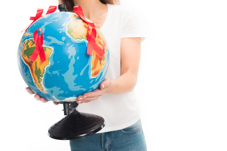 cropped image of woman in white shirt holding globe with red ribbons isolated on white, world aids day concept