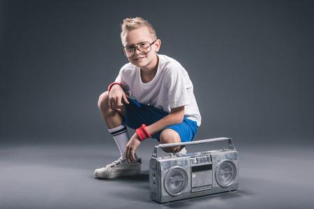 stylish preteen boy in eyeglasses with boombox posing on grey backdrop Stock Photo