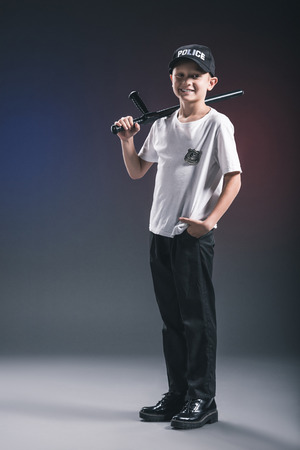 smiling boy in white tshirt and cap police officer uniform with truncheon in dark backdrop