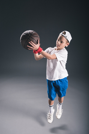 stylish boy playing basketball on grey background