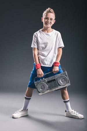 stylish smiling boy in eyeglasses with boombox posing on grey backdrop