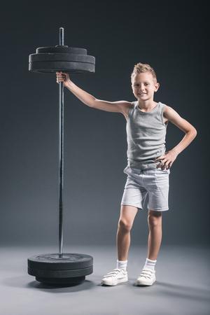 smiling pre-adolescent boy in sportswear standing near barbell on dark backdrop