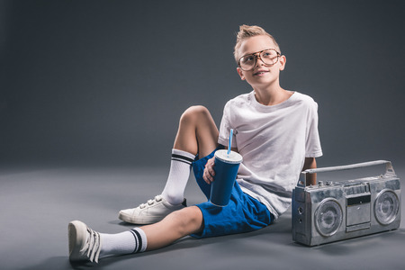 stylish boy in eyeglasses with soda drink and boombox on grey background