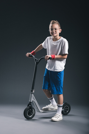 smiling stylish boy in eyeglasses on scooter looking at camera on grey backdrop Imagens