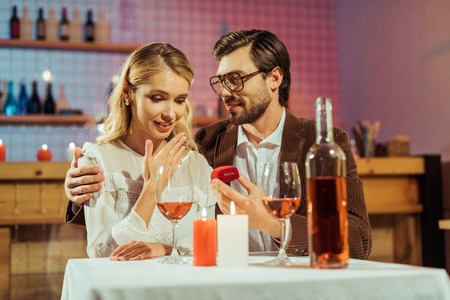 handsome man proposing to beautiful girlfriend during romantic dinner in cafe