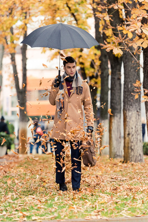 handsome man in coat with umbrella standing on autumnal street with golden leaves falling from above