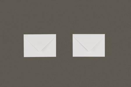 close-up view of two white envelopes arranged isolated on grey background 스톡 콘텐츠