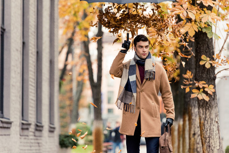 stylish man in coat with golden leaves falling from umbrella standing on autumnal street