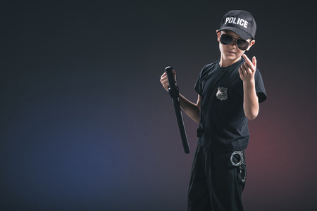 portrait of boy in policeman uniform and sunglasses gesturing on dark background