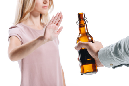 cropped image of blonde woman rejecting bottle of unhealthy beer isolated on white Stock Photo