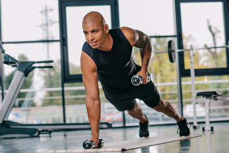 smiling muscular african american sportsman exercising with dumbbells on fitness mat at gym