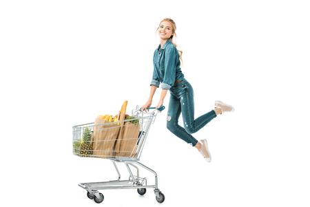 happy young woman jumping near shopping trolley cart with products in paper bags isolated on white Stockfoto