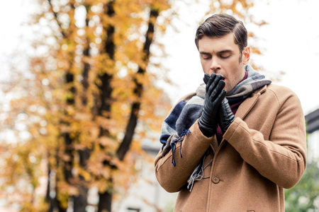 bottom view of stylish man in coat freezing on autumnal street