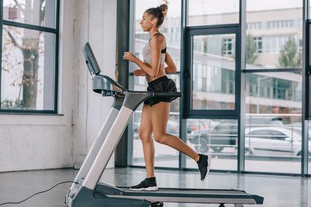 side view of african american sportswoman running on treadmill at gym Zdjęcie Seryjne