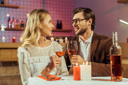 smiling couple clinking by wine glasses at table with candles in restaurant