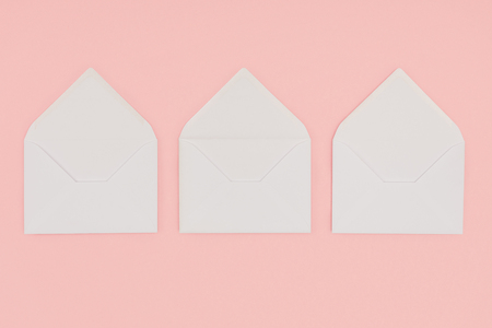 top view of open white envelopes isolated on pink
