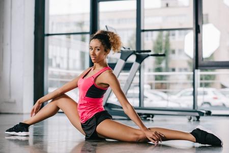 mooie Afro-Amerikaanse Sportvrouw die zich uitstrekt op de vloer in de sportschool