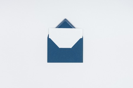 close-up view of blue open envelope with blank white card isolated on white