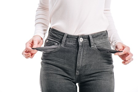 cropped image of woman showing empty pockets isolated on white