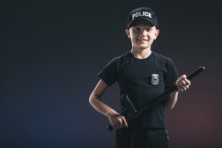 smiling preteen boy in policeman uniform with truncheon on dark backdrop