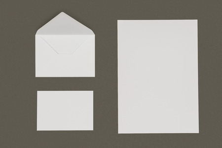 top view of open white envelope, blank card and paper sheet isolated on grey